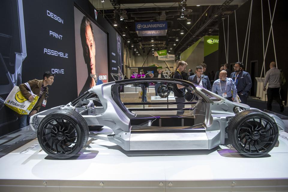 Attendees view vehicles manufactured by 3D printing design at the 2017 Consumer Electronics Show